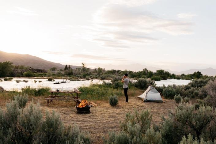 Kampeer met Tent en kampvuur langs rivier